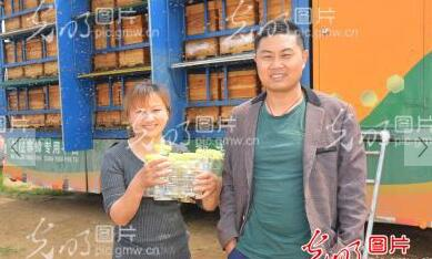 郭龙和妻子陈根英在养蜂车前合影